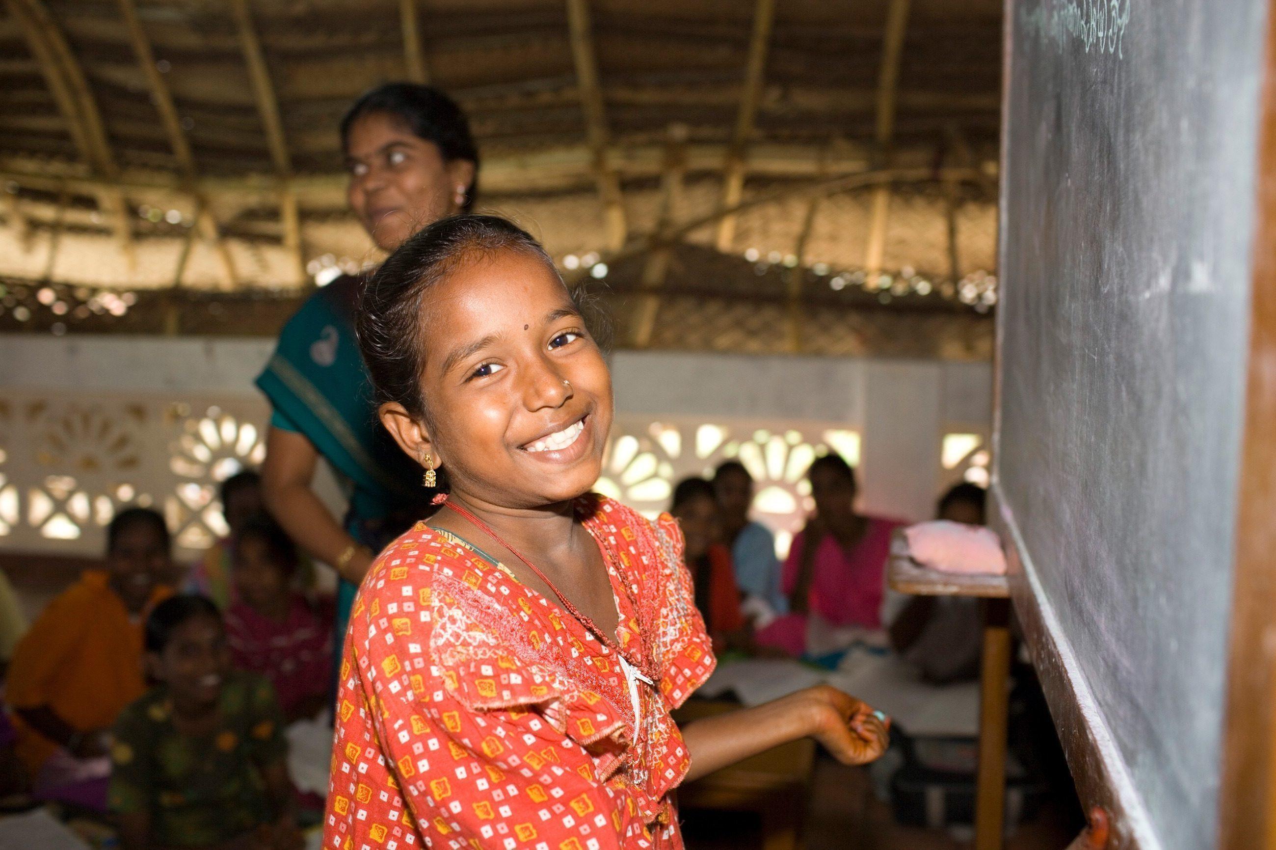 Ein indisches Mädchen steht lächelnd an der Tafel.