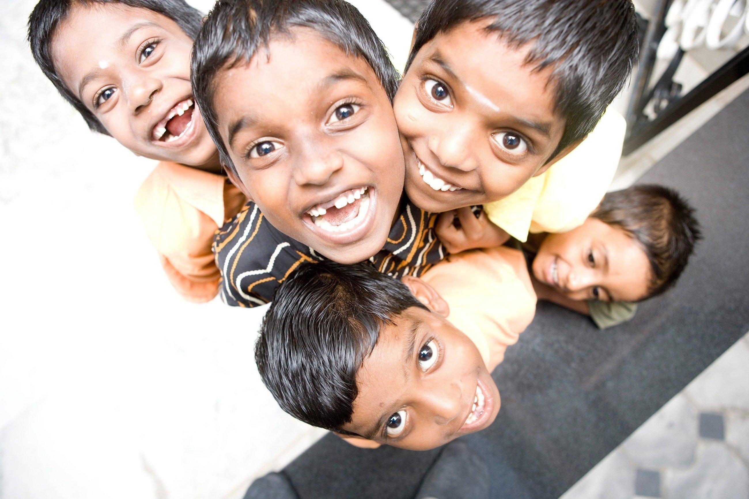 Indische Kinder schauen lachend nach oben in die Kamera.