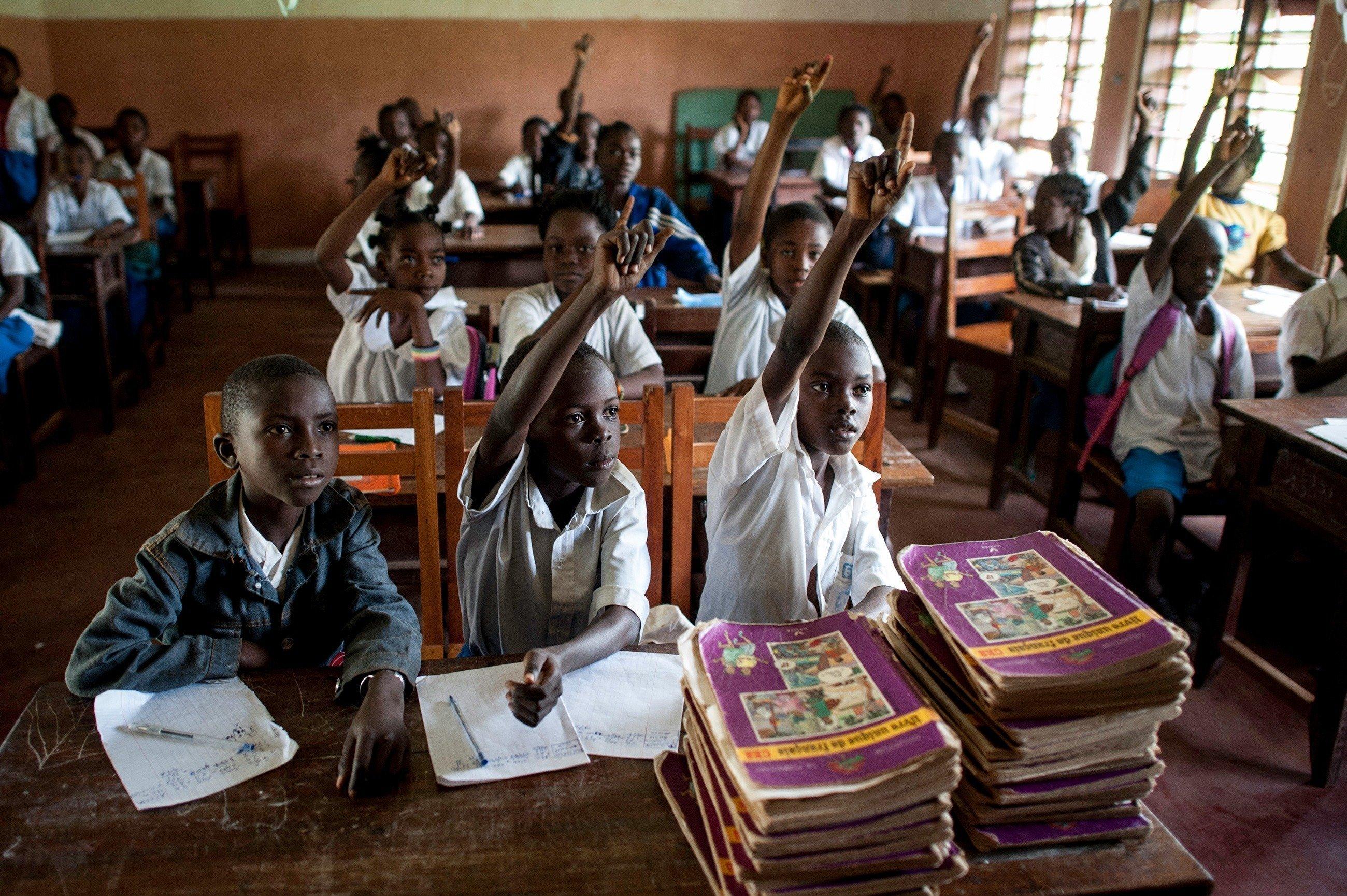 Afrikanische Schüler melden sich im Unterricht.