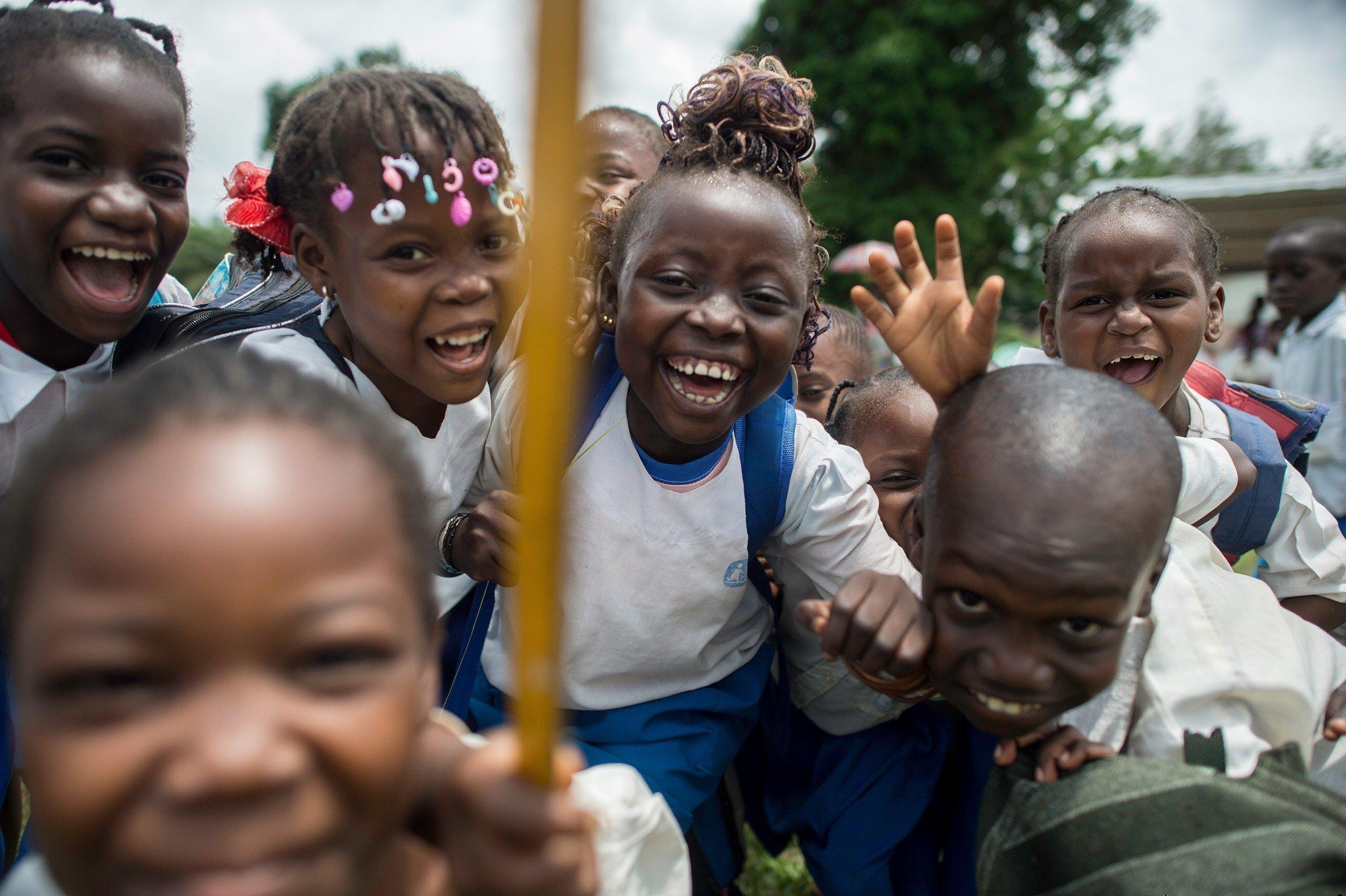 Gruppe afrikanischer Kinder lacht ausgelassen.