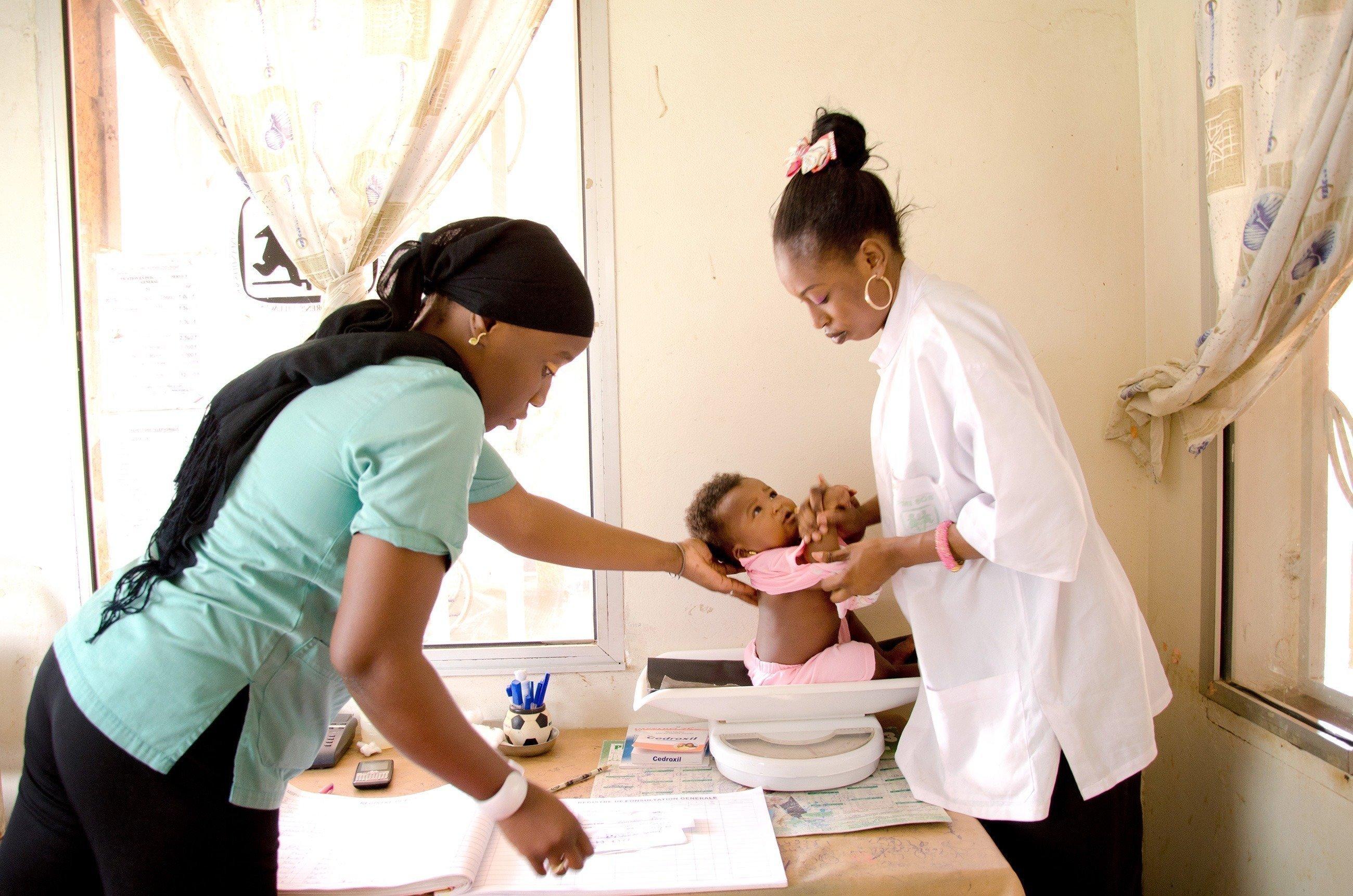 Baby wird von Krankenschwestern gewogen.
