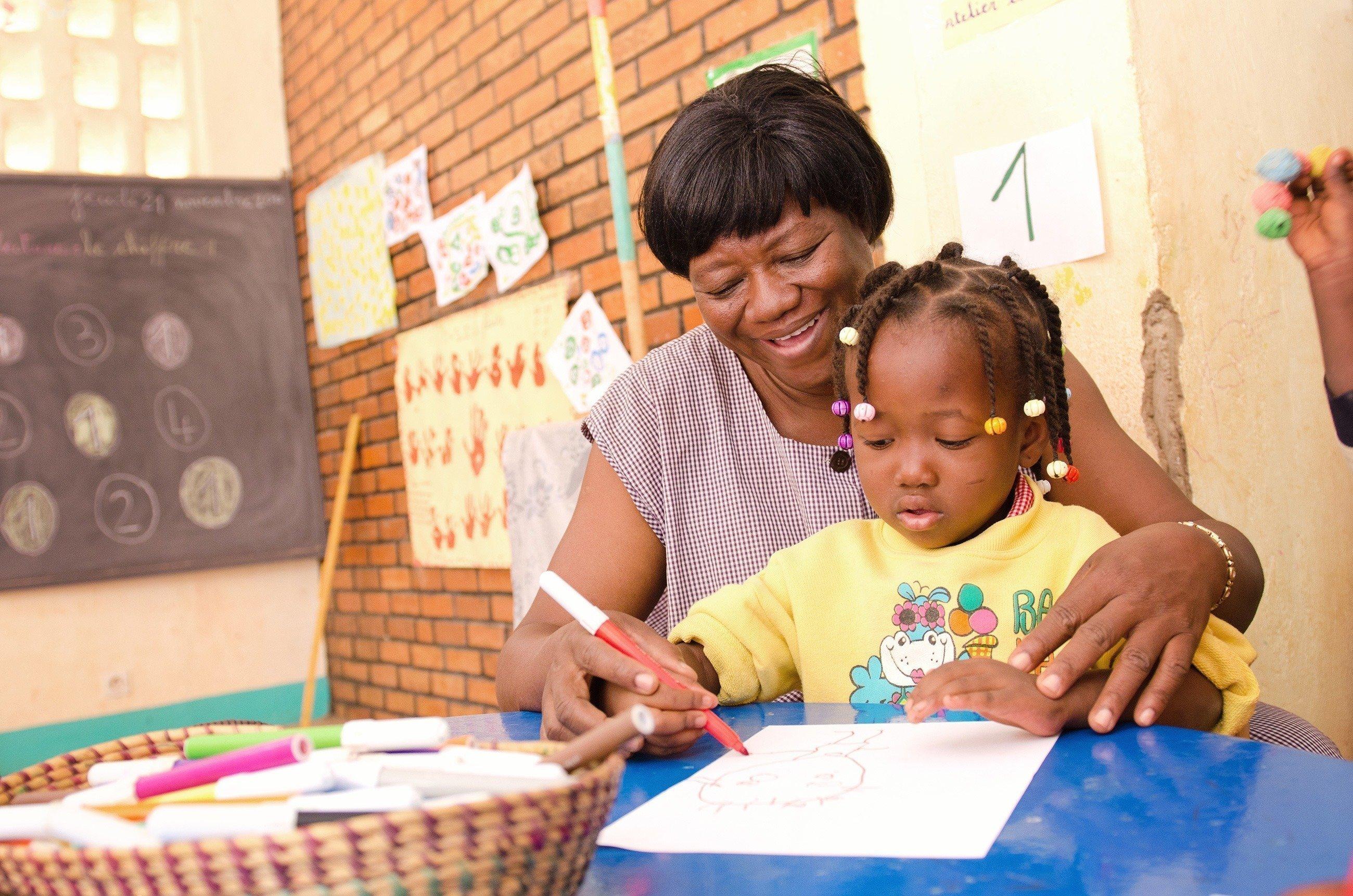 Mädchen übt das Malen auf dem Schoß ihrer Mutter.
