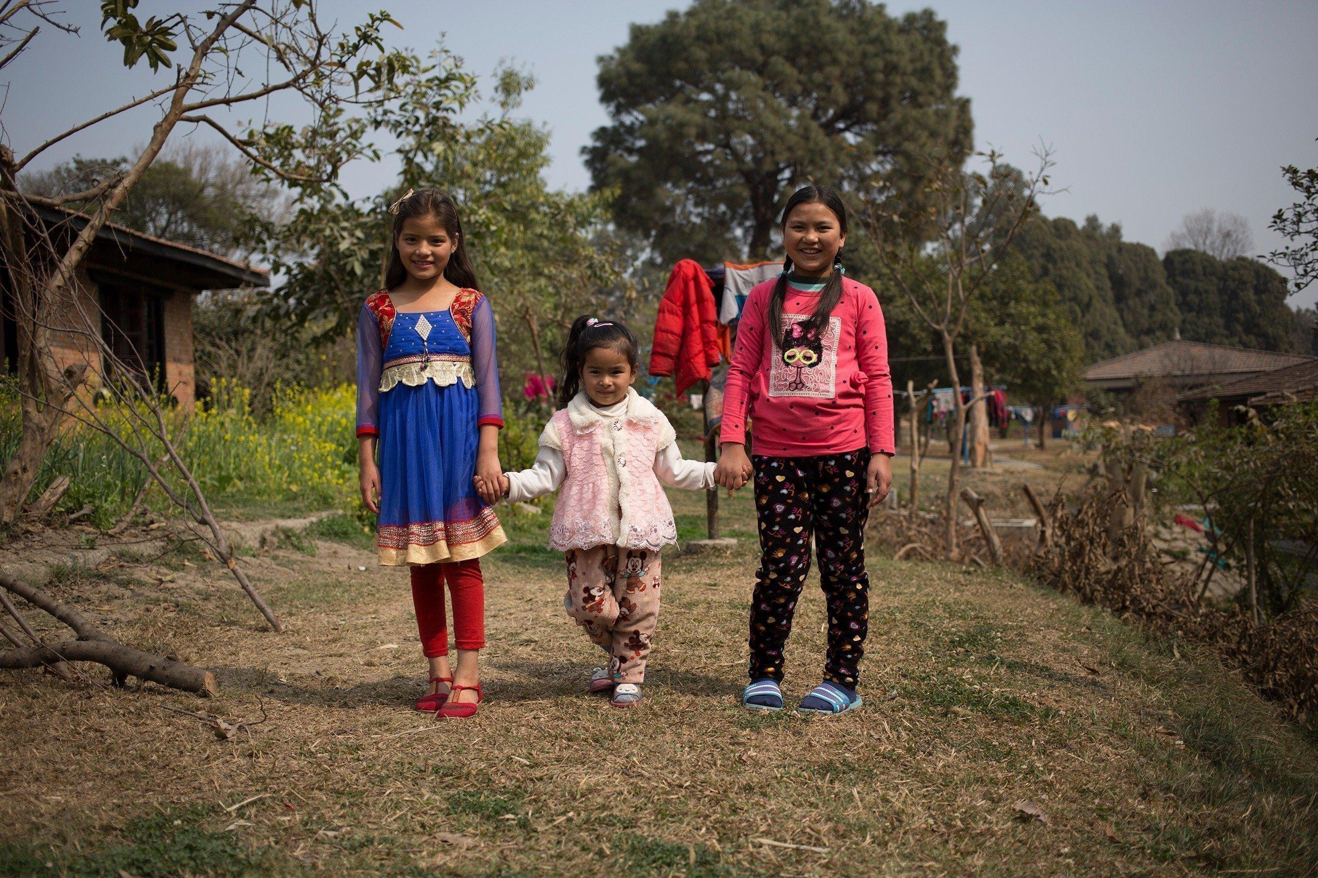 Drei Mädchen unterschiedlichem Alters fassen sich an den Händen.