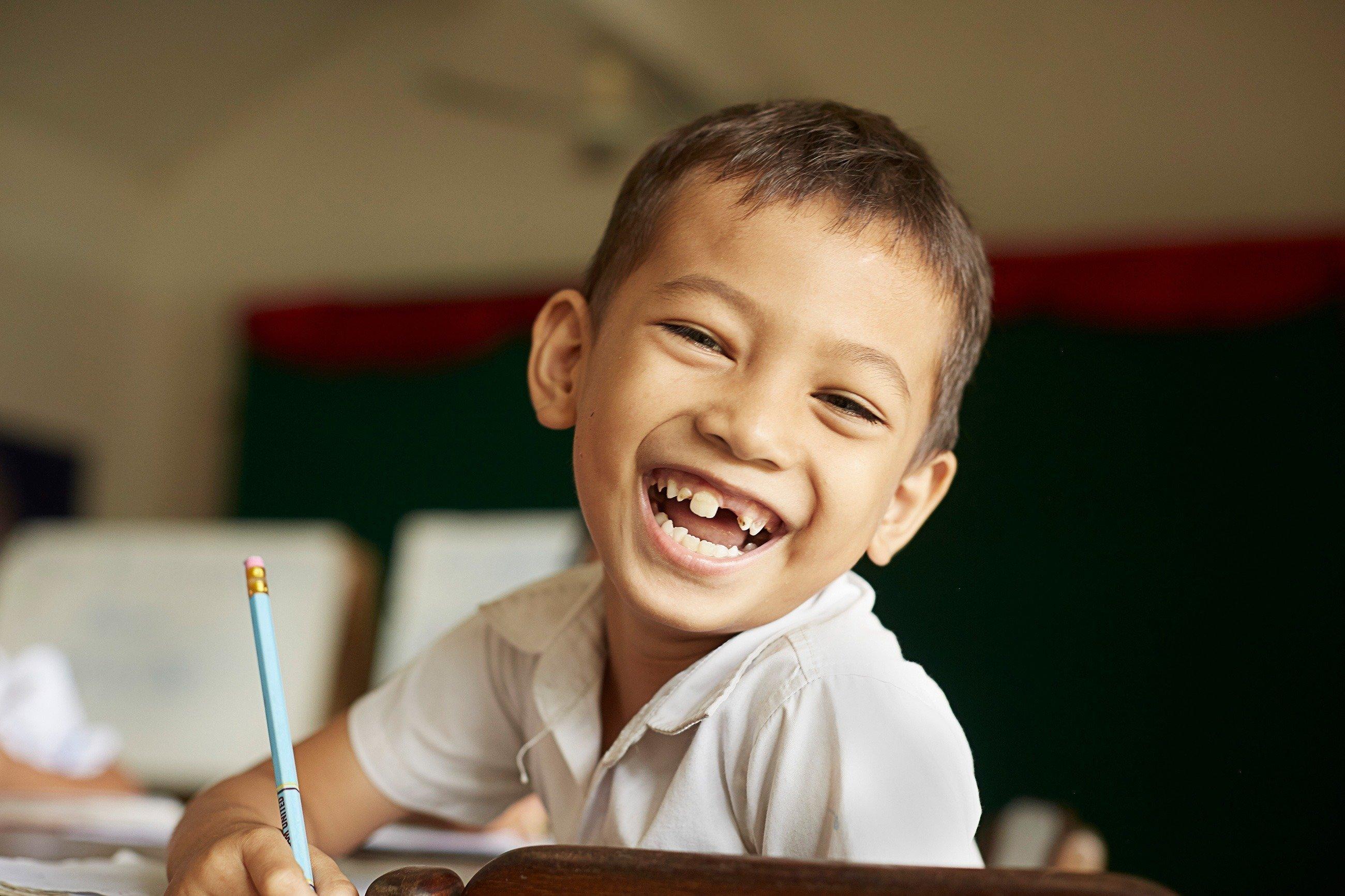 Schuljunge mit großer Zahnlücke lacht in die Kamera.
