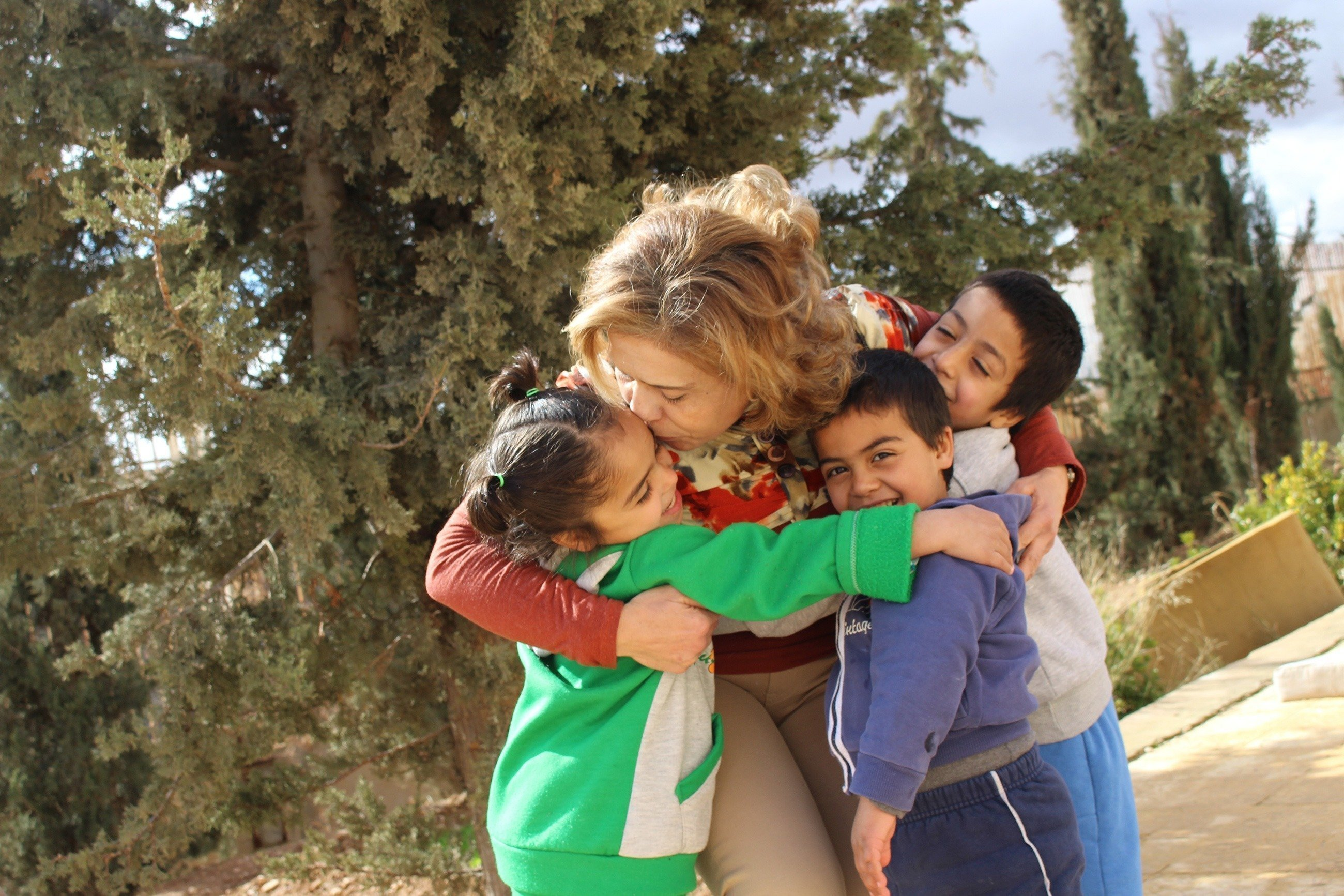 SOS-Kinderdorf Mutter umarmt und küsst drei Kinder.