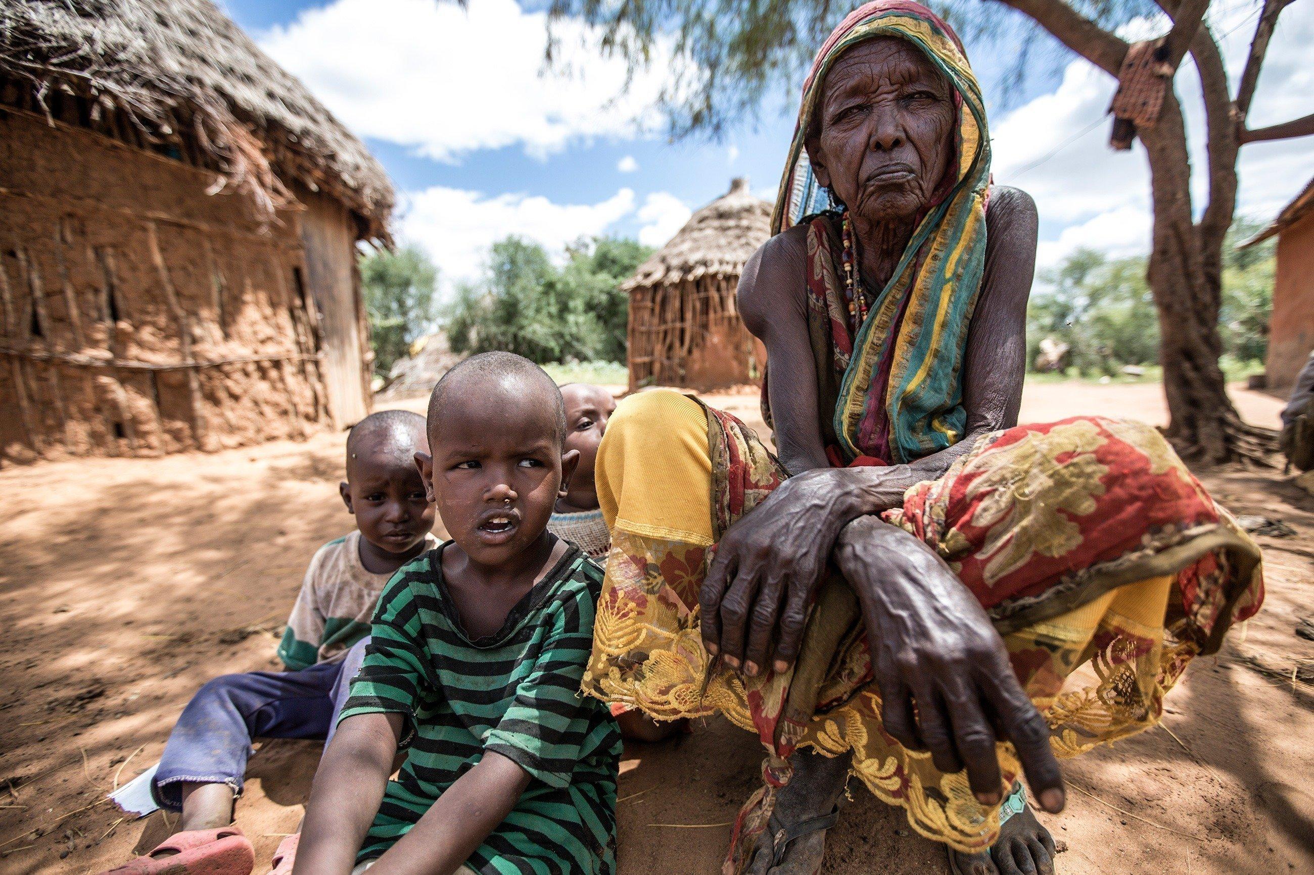 Eine alte Frau sitzt mit zwei Kleinkindern im Schatten eines Baumes.