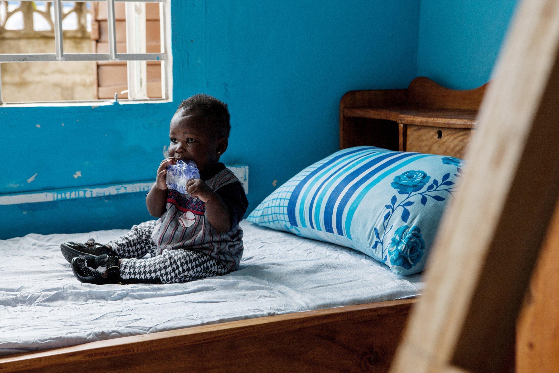 Kleiner afrikanischer Junge sitzt auf dem Bett und kaut an einem Stück Plastik.
