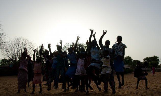 Afrikanische SOS-Kinderdorf Schulklasse springt in die Luft und jubeln.