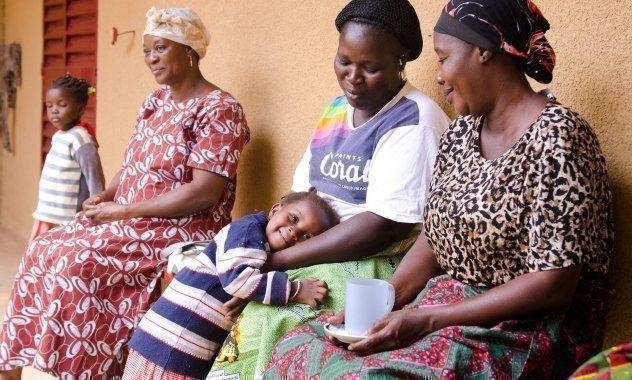 Drei Afrikanische SOS-Kinderdorf Mütter sitzen auf einer Bank vor einem Haus. Eine Mutter umarmt ihr Kind.