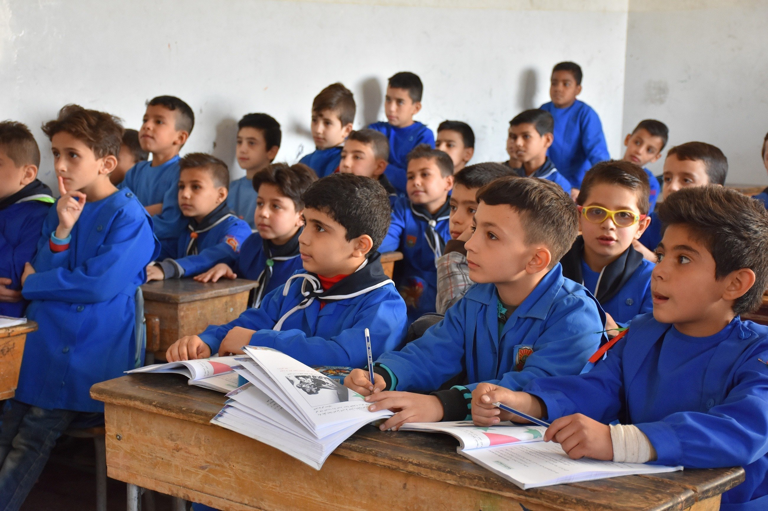 Eine Gruppe Jungen hören in der Schule aufmerksam zu.