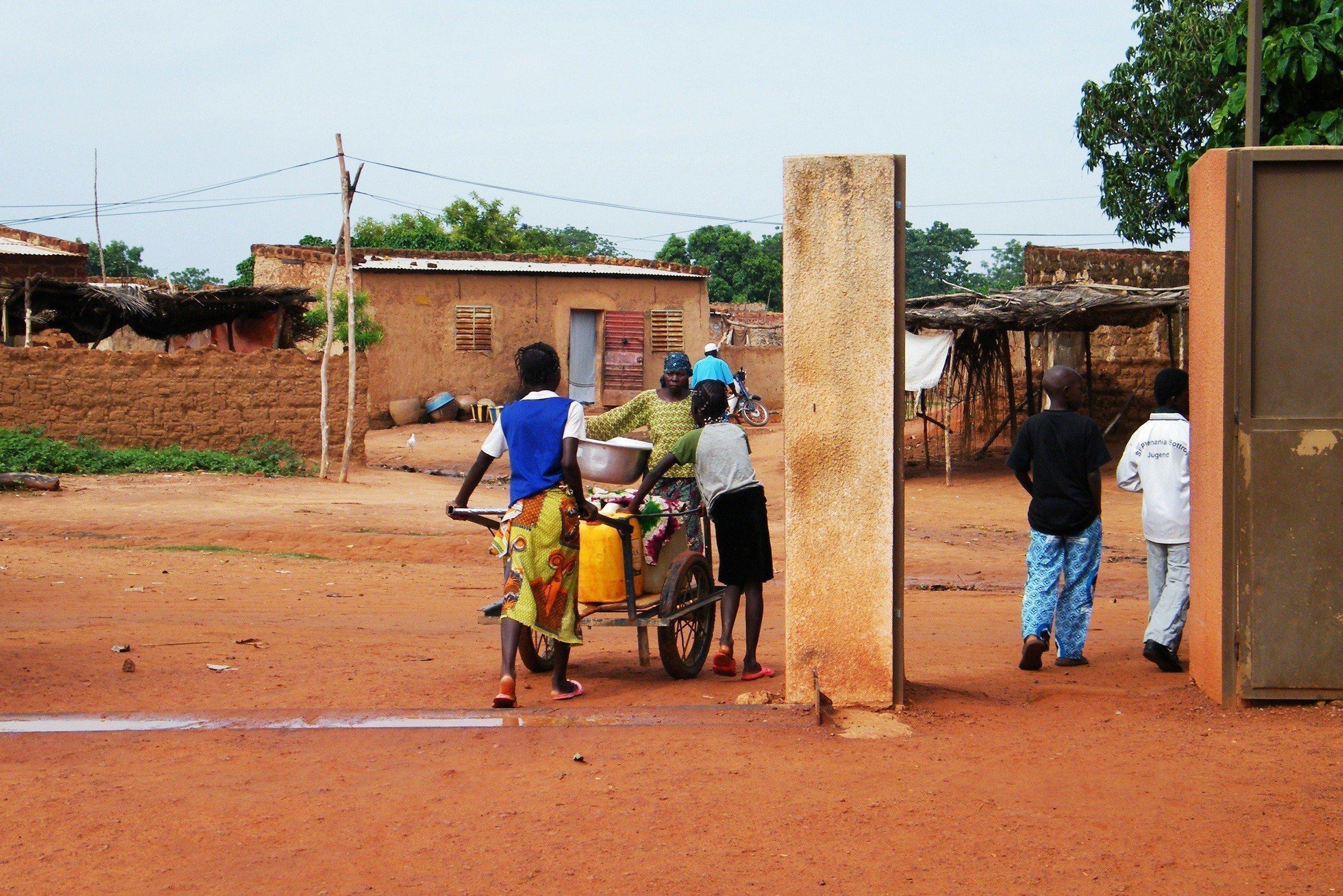Menschen mit einem Handkarren an einer Wasserstation.