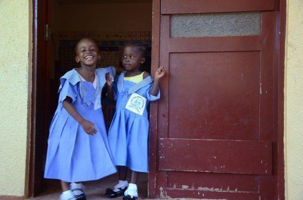 Zwei kleine Mädchen mit blauen Kleidern stehen in einer Tür.