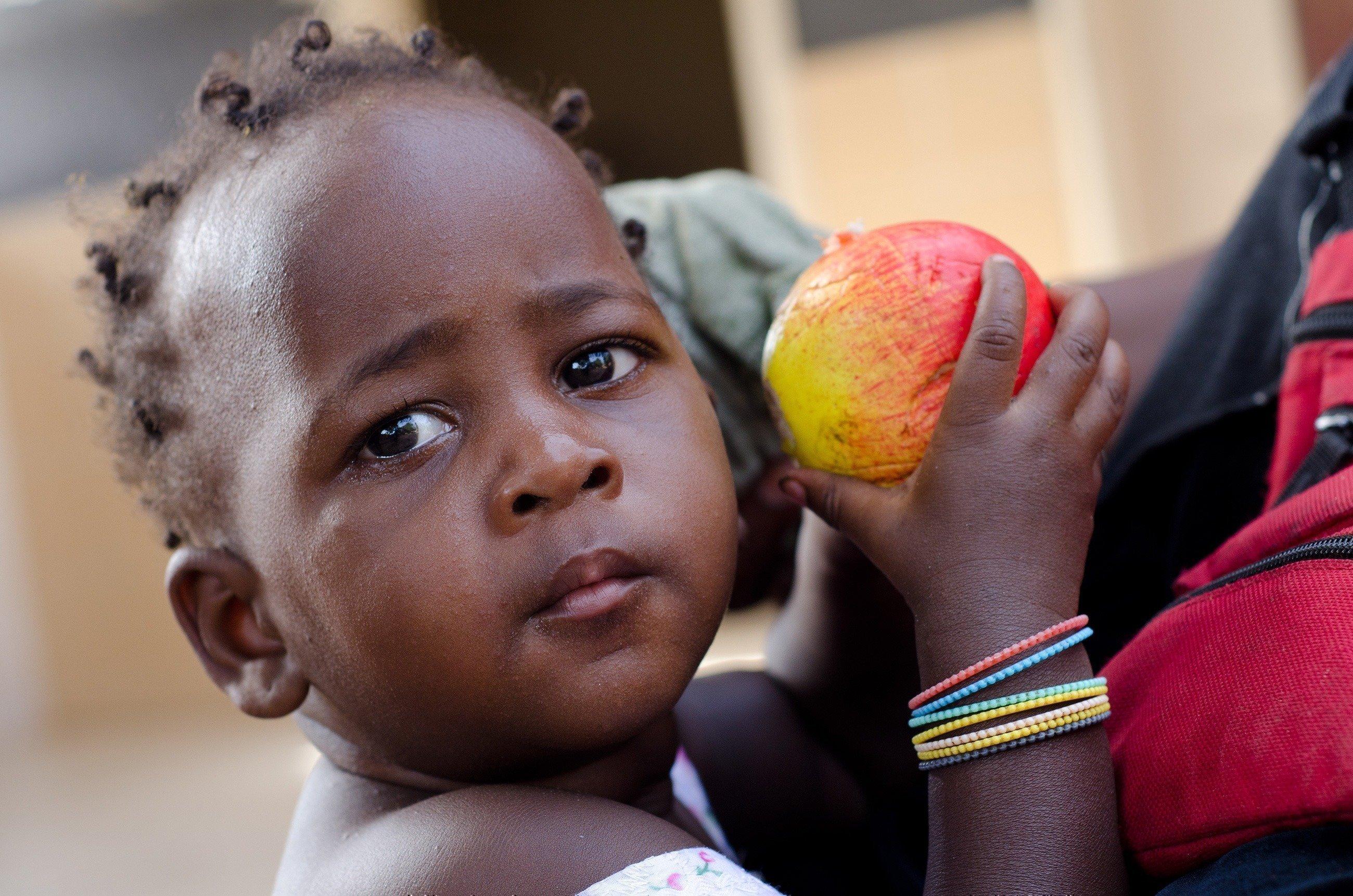 Kleines Mädchen mit einem Apfel in der Hand.