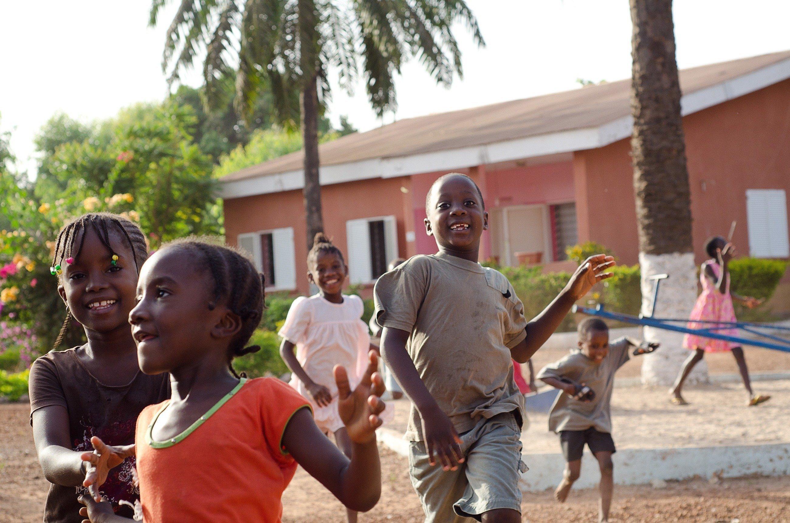 Draußen spielende afrikanische Kinder vor einem Haus.