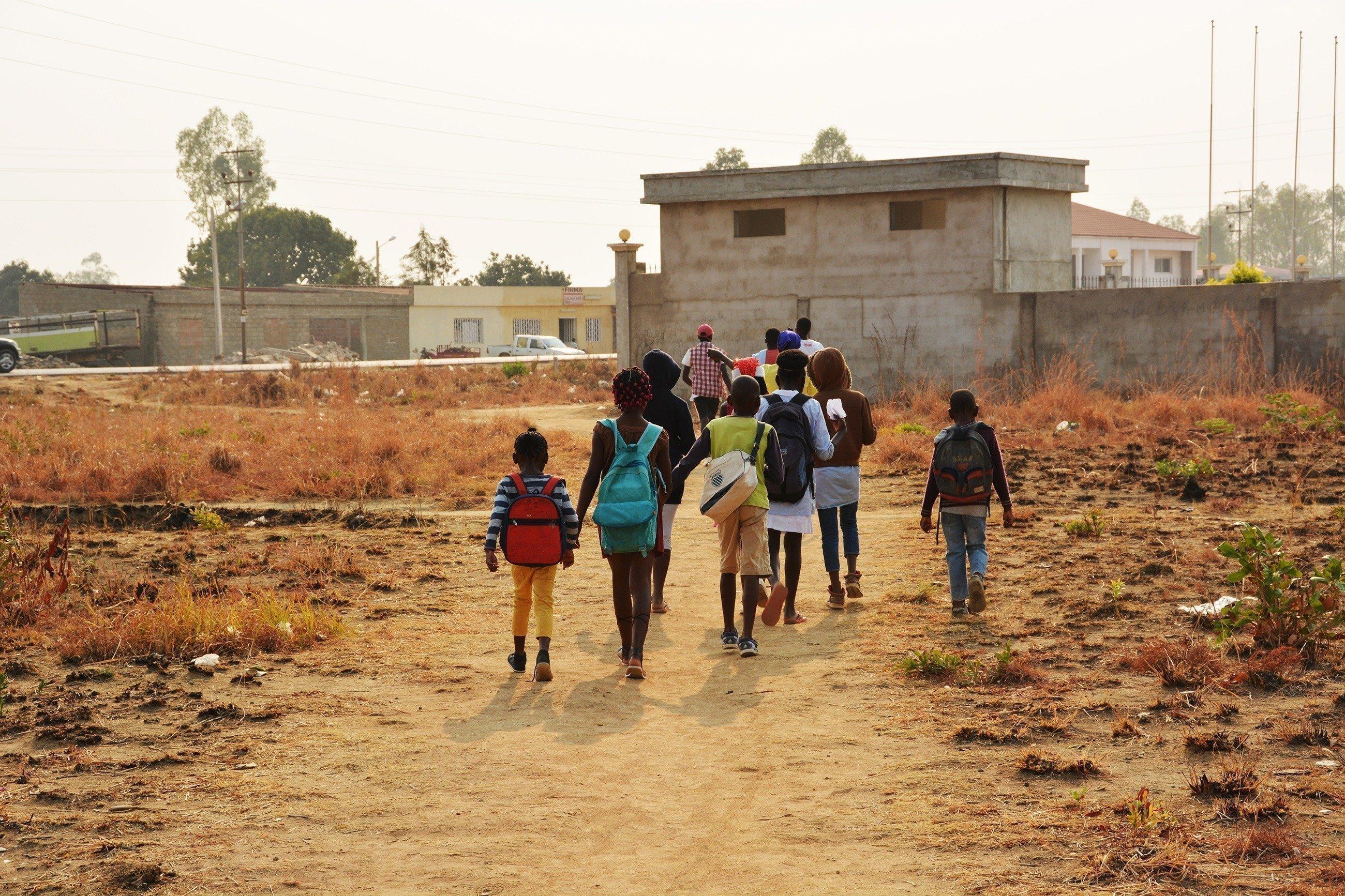 Mehrere Kinder mit Rucksäcken gehen in die Richtung eines Schulgebäudes.