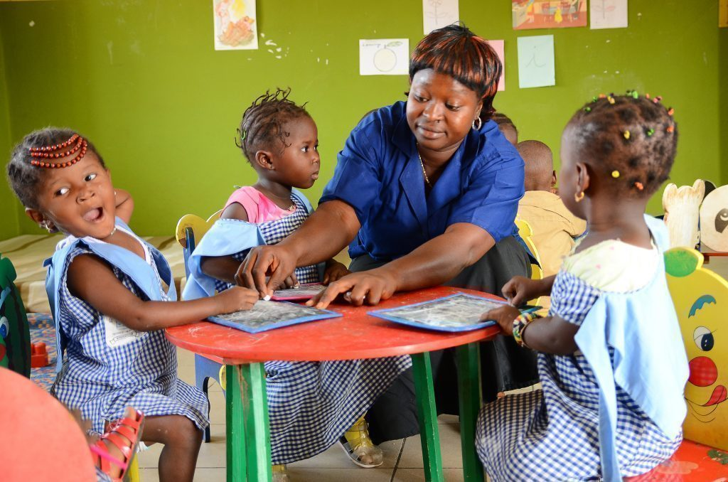 Mutter malt mit ihren Kindern am Tisch