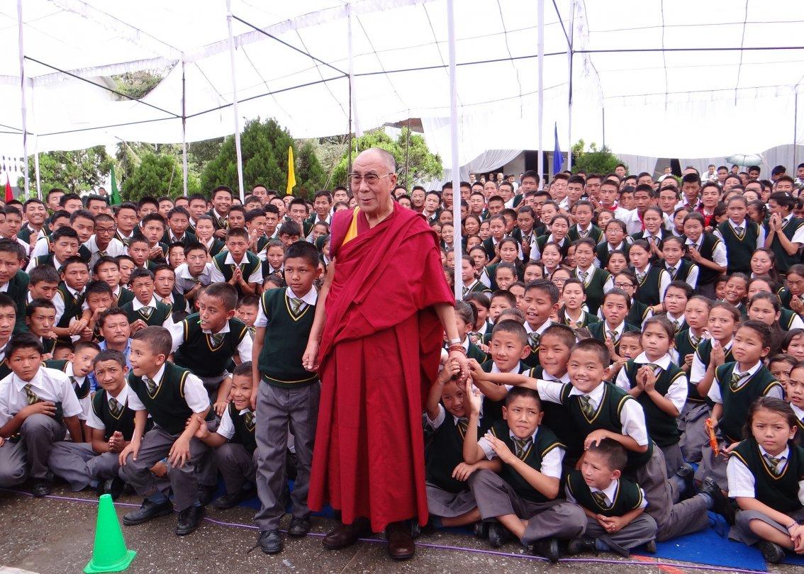 Dalai Lama steht vor hunderten von SOS Kinderdorf Schülern.