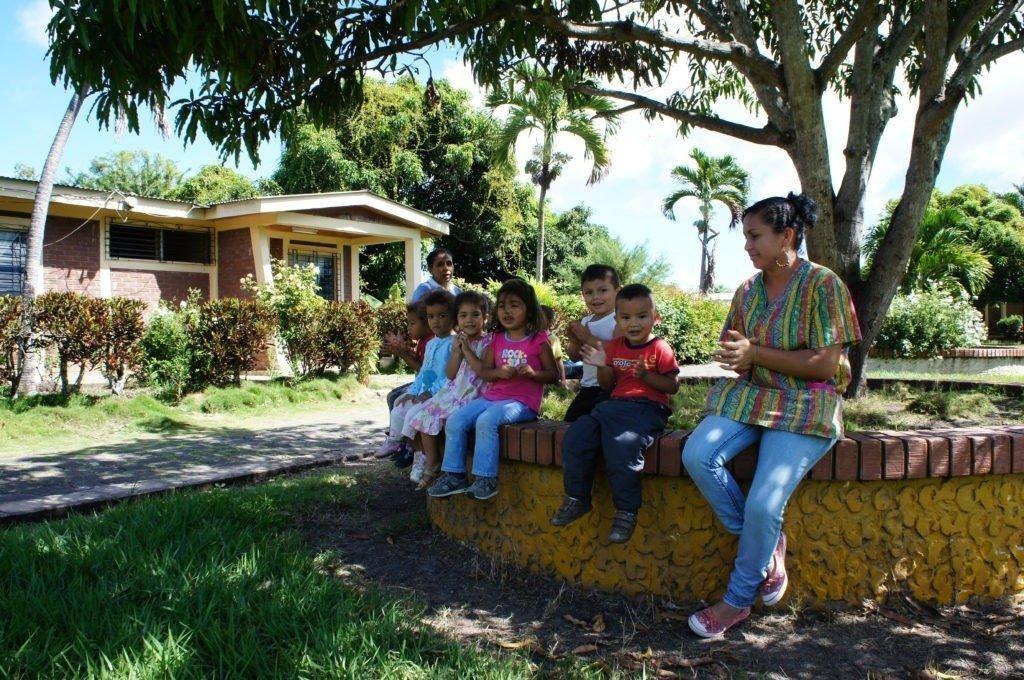 Gruppe von Kindern sitzen im Freien auf einer Mauer unter einem Baum