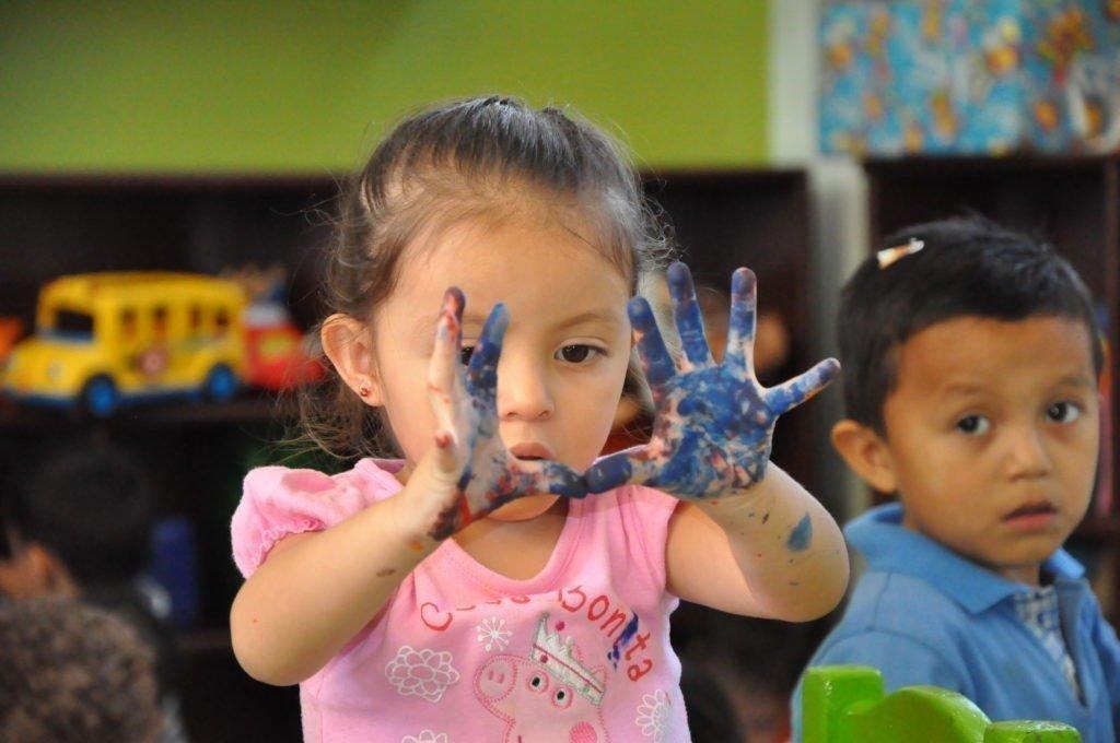 kleines Mädchen zeigt ihre blauen Hände hoch.
