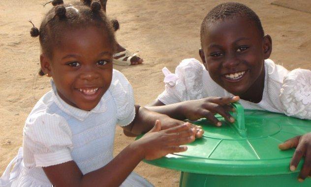 Zwei lachende Kinder sitzen vor einem Spielzeug.