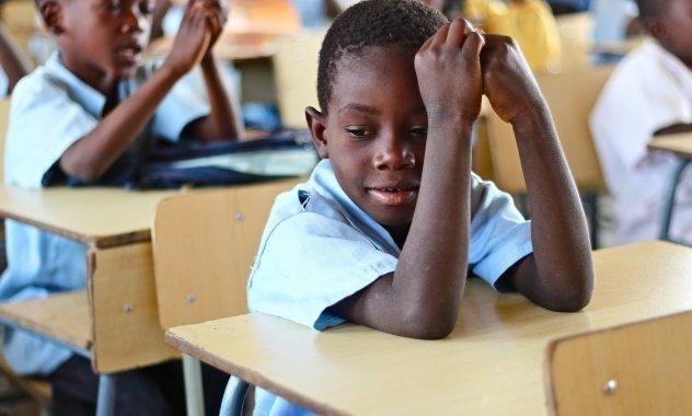 Ein kleiner Junge sitzt in Uniform in der Schule.