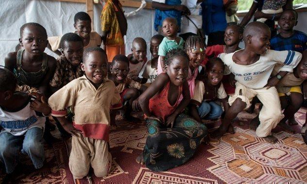 Gruppe von Kindern sitzt auf einem Teppich und schaut in die Kamera.