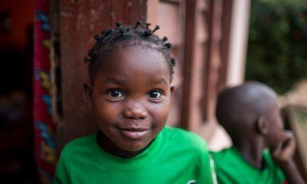 Kleiner Junge mit grünem Shirt lächelt.