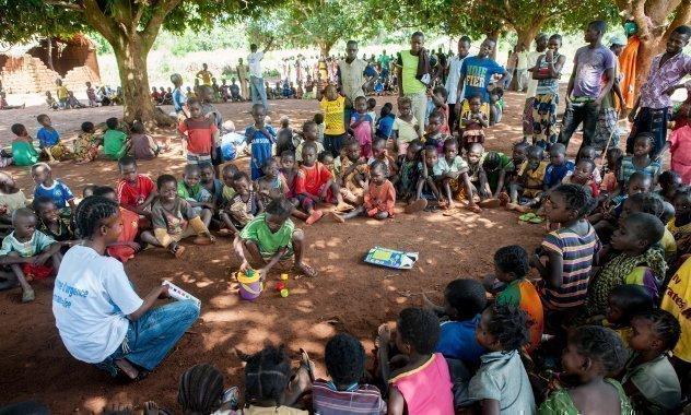 Kinder sitzen im Kreis mit einer Betreuerin von SOS-K.