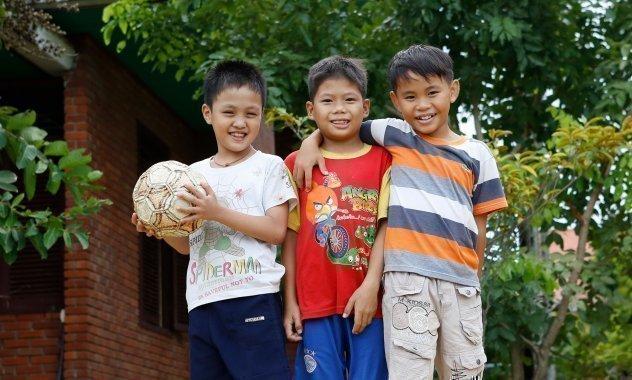 Drei Jungen mit einem Fußball.