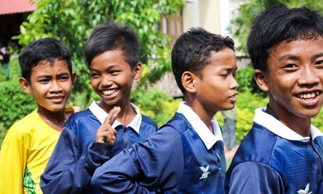 Jungen, die Fußball spielen, lachen.