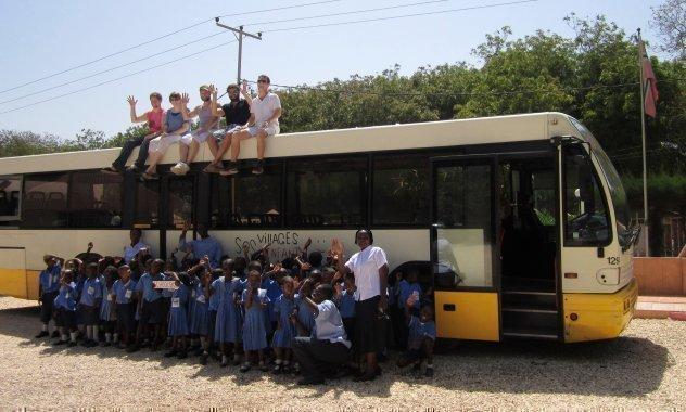 Vor einem Reisebus steht eine Schulklasse, sowie auf ihm einige SOS-Mitarbeiter sitzen.