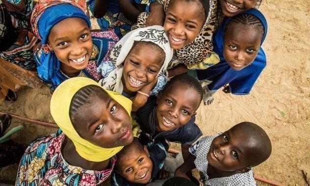 Kinder aus SOS-Kinderdorf in Kenya schauen in eine über ihnen hängende Kamera.