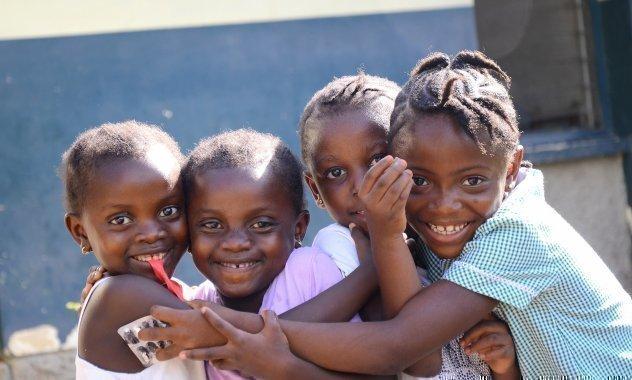 Vier SOS-Kinderdorf Kinder schauen in die Kamera und lachen.