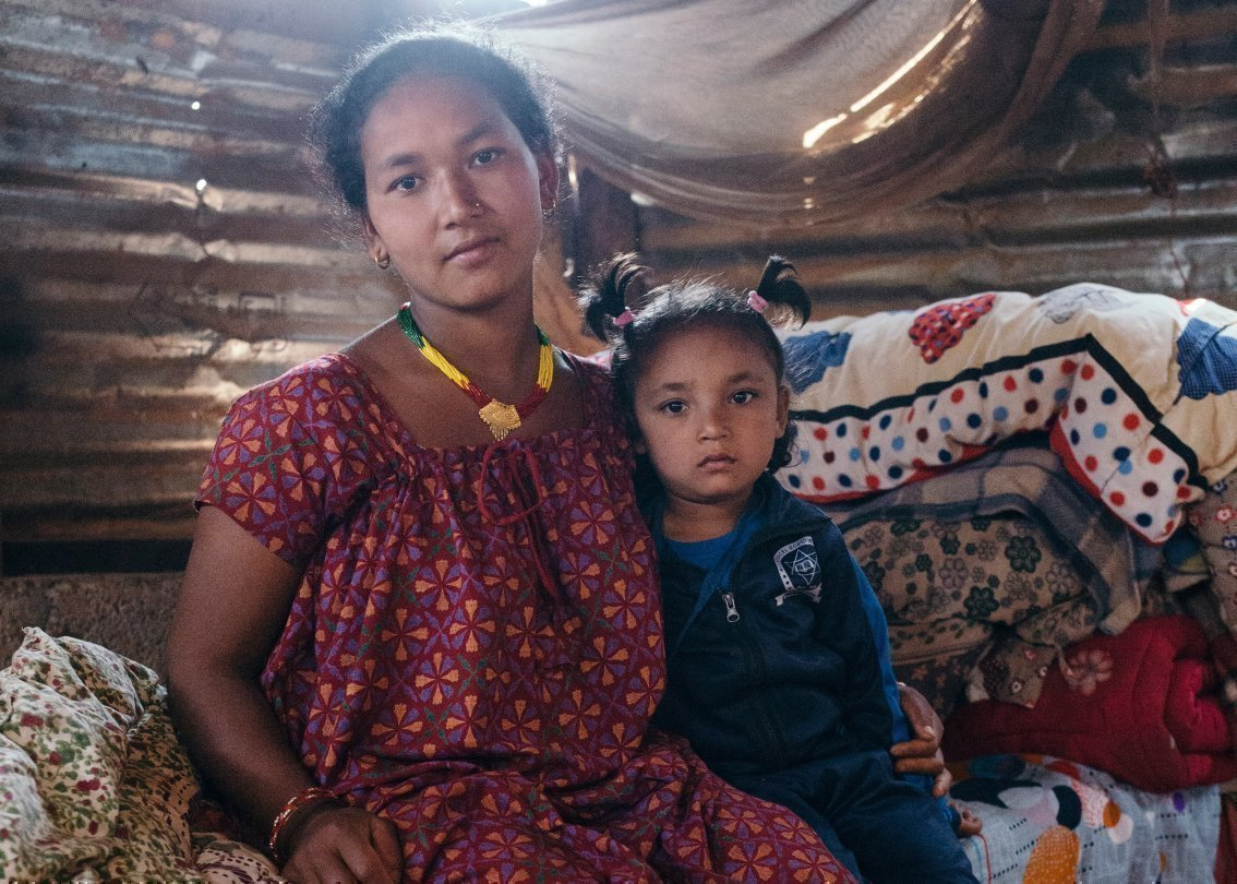 Eine Mutter aus Nepal mit ihrer Tochter im Arm.