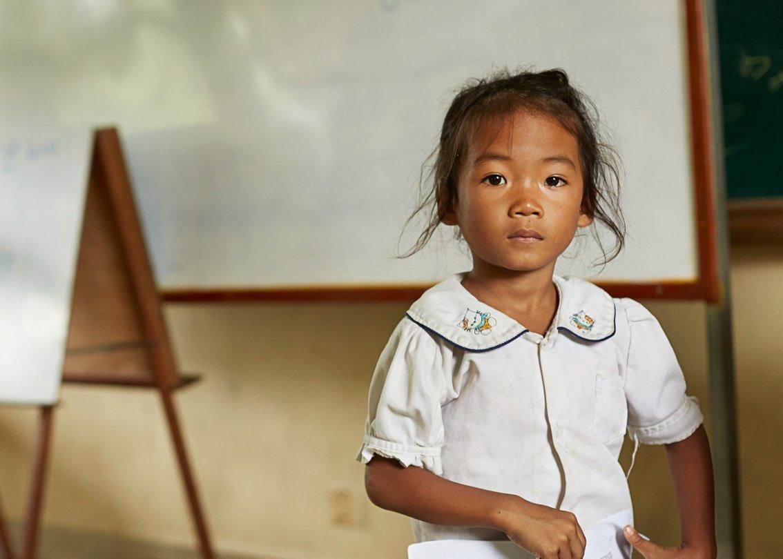 Kleines Mädchen steht vor einer weißen Schultafel.