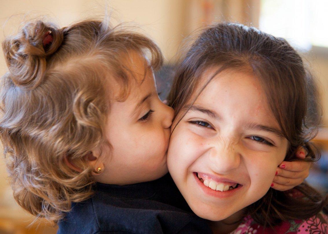 Ein kleines Mädchen küsst ein anderes Mädchen auf die Wange.