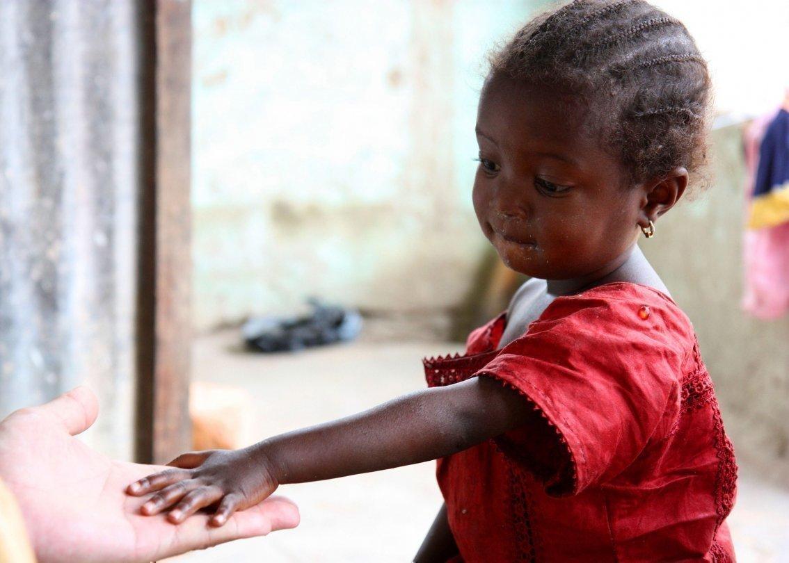 Afrikanisches kleines Mädchen reicht einem Paten die Hand.