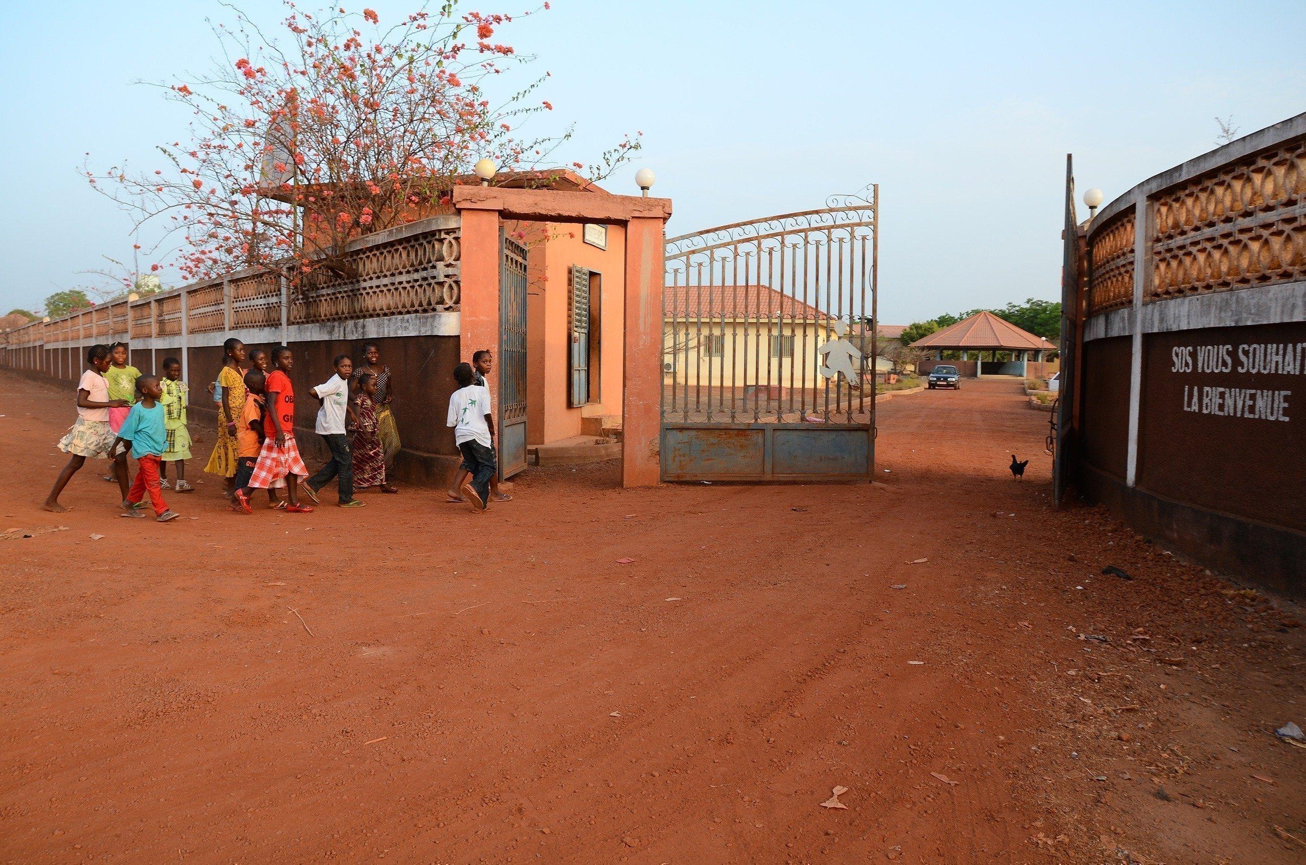 Bambini corrono attraverso il cancello d'ingresso di un SOS Villaggio dei Bambini.