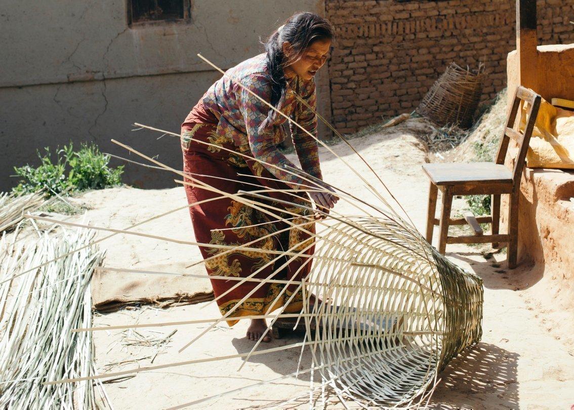 Eine Frau flechtet einen Korb.