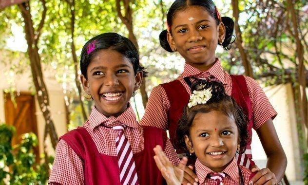 Drei adrett in Schuluniform gekleidete Mädchen.