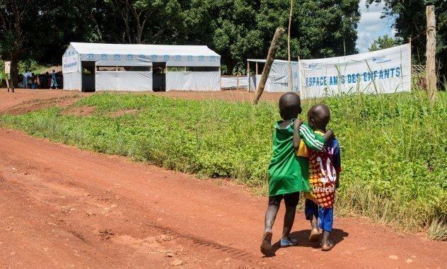 Zwei Jungen schauen zu einem SOS-Kinderdorf.