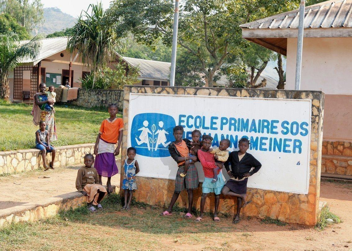 SOS-Kinderdorf Kinder vor dem Kinder Dorf-Schild.