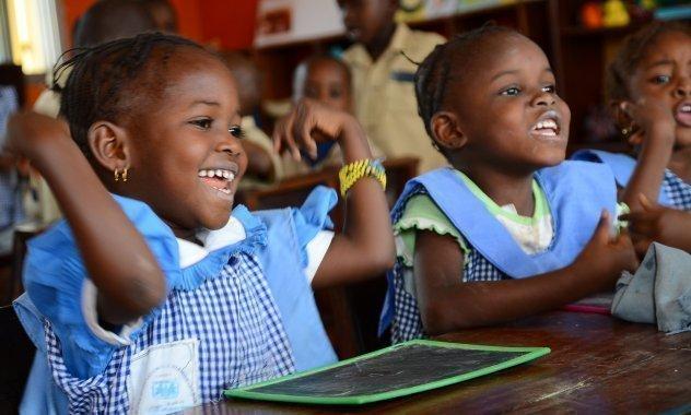 Zwei kleine Mädchen in der Schule, haben Spass am lernen.