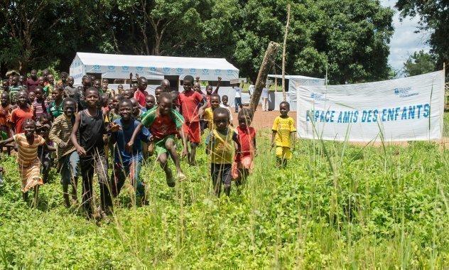Viele Kinder laufen auf die Kamera zu. Ein Eingangsschild zeigt einen SOS-kinderdorf Slogan.
