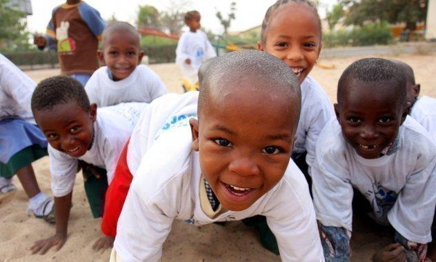 Mehrere Kinder lachen beim Spielen in die Kamera.