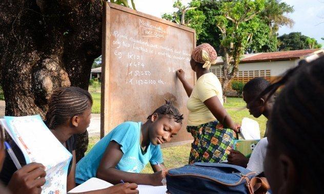 Kinder lernen mit einer Tafel.