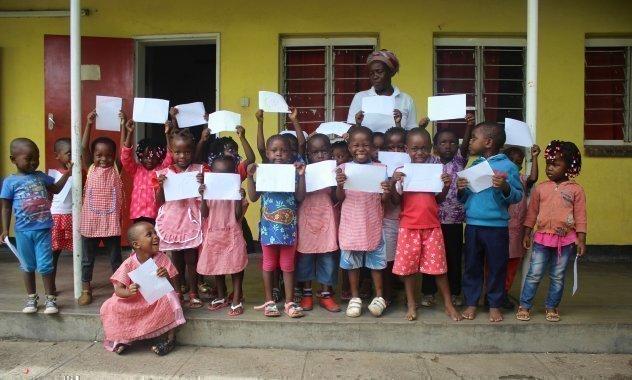 Afrikanische SOS-Kinderdorf Schulklasse halten IHre Zeugnisse hoch.