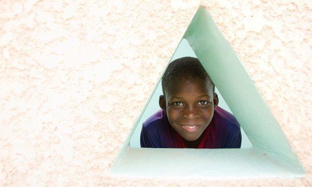 Junge schaut durch ein Fenster in Dreiecks-Form.