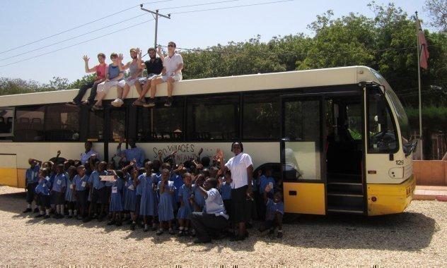 Afrikanische SOS-Kinderdorf Schulklasse bei einem Ausflug vor einem Bus.
