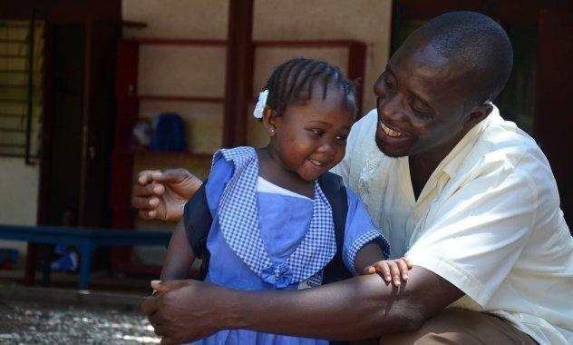 Afrikanischer Vater hält sein Schulkind im Arm.